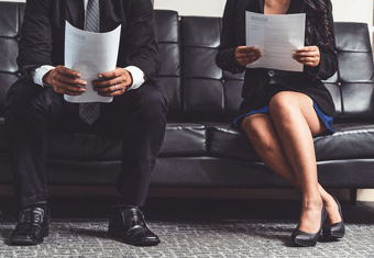Job seekers sit on a sofa before their job interviews.